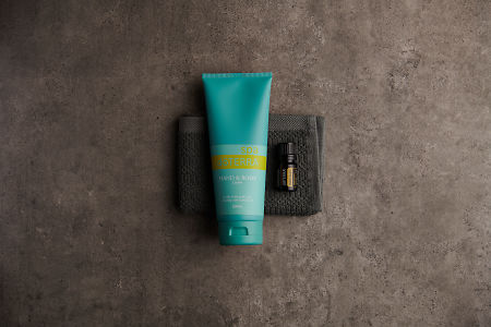 doTERRA Spa Hand and Body Lotion with Helichrysum essential oil on a gray washcloth on a stone background.