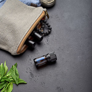 doTERRA Ice Blue with clutch, accessories and mint leaves on a black concrete background.