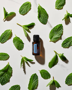 doTERRA Peppermint essential oil and peppermint leaves in direct sunlight on a white marble background.