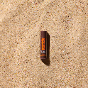 doTERRA Spa Tropical Lip Balm in direct sunlight on the beach.