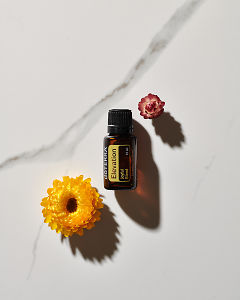 doTERRA Elevation essential oil blend and two flowers in direct sunlight on a white marble background.
