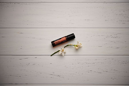 doTERRA Neroli Touch with orange blossoms on a white wooden background.