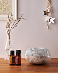 doTERRA Brevi Stone diffuser with Tangerine and Wintergreen essential oils and holiday decorations on a side table.