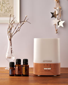 doTERRA Lumo diffuser with Juniper Berry, Grapefruit and Wild Orange essential oils and holiday decorations on a side table.