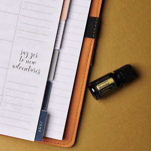 doTERRA Manuka and an open journal with an inspirational quote on a golden background.