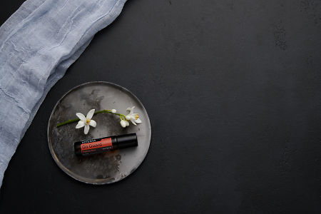 doTERRA On Guard Touch with orange blossom flowers on a ceramic plate on a black concrete baclground.