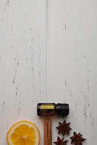 doTERRA Cheer with a vanilla bean, cinnamon stick and star anise on a white wooden background.