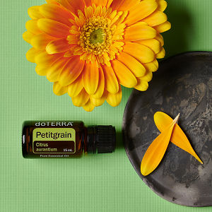 doTERRA Petitgrain with a yellow flower in close up and petals on a ceramic plate on a green textured background.