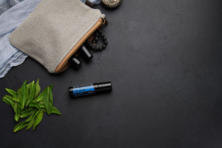 doTERRA Ice Blue Roll On with clutch, accessories and mint leaves on a black concrete background.