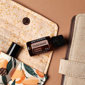 doTERRA Cedarwood on an essential oil bag with a diary on a brown textured background.