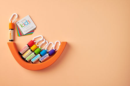 doTERRA Kids Oil Collection  oils with caps and carabiners and flashcards, featuring Brave, on a pale orange paper background.