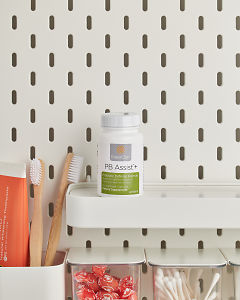 doTERRA PB Assist+ on a bathroom shelf with additional doTERRA products and bathroom accessories.