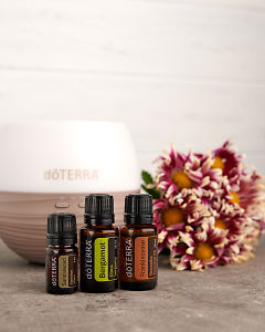 doTERRA Sandalwood, Bergamot and Frankincense with a Petal dffuser and a bunch of flowers on a gray stone benchtop.