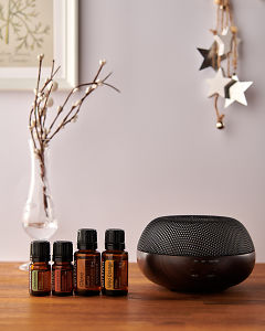 doTERRA Brevi Walnut diffuser with Cardamom, Cinnamon, Clove and Wild Orange essential oils and holiday decorations on a side table.