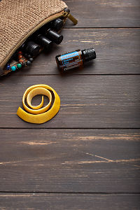 doTERRA Breathe, lemon peel and clutch with oils on brown wooden background.