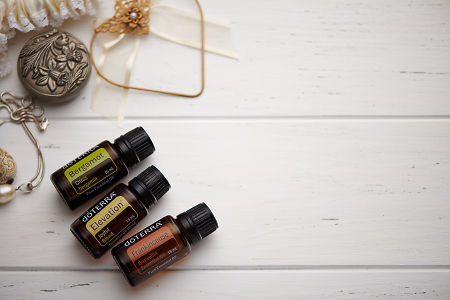 doTERRA Bergamot, Elevation and Frankincense oils and wedding accessories on white rustic wooden background.