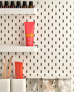 doTERRA Spa Rose Hand Lotion on a bathroom shelf with bathroom accessories and additional doTERRA products.