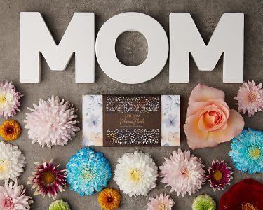 doTERRA Precious Florals Collection with the letters M O M surrounded by flowers on a gray stone background.