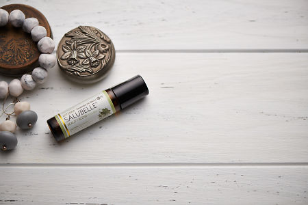doTERRA Salubelle blend, jewellery and trinkets on white rustic wooden background.