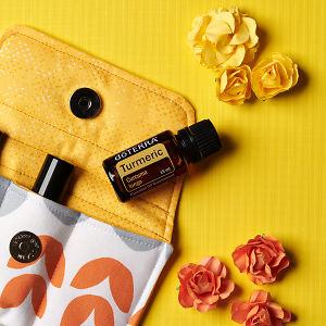 doTERRA Turmeric on an essential oil bag with scattered flowers on a yellow textured background.
