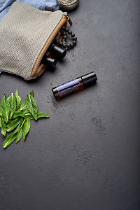 doTERRA PastTense with clutch, accessories and mint leaves on a black concrete background.