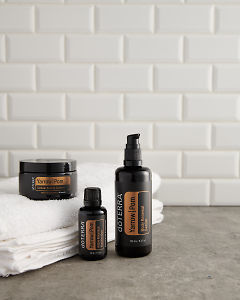 doTERRA Yarrow Pom, Body Renewal Serum and Cellular Beauty Capsules with a white towel on a gray stone bathroom bench top.
