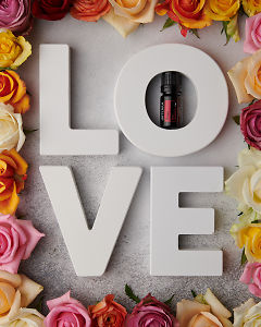 doTERRA Rose with the letters L O V E surrounded by roses on a white concrete bench top.