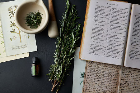 doTERRA Rosemary with vintage books, illustrations, a mortar and pestle and a rosemary branch on a black stone background.