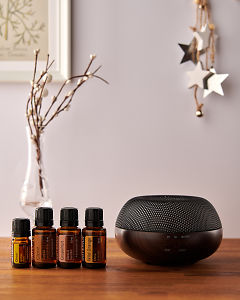 doTERRA Brevi Walnut diffuser with Cheer, Clove, Grapefruit and Wild Orange essential oils and holiday decorations on a side table.
