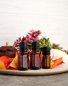 doTERRA Clary Sage, Geranium and Kumquat with flowers and a banksia seed pod diffuser on a gray stone bench.