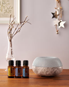 doTERRA Brevi Stone diffuser with Lemon, Peppermint and Ylang Ylang essential oils and holiday decorations on a side table.
