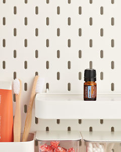 doTERRA Whisper Blend for Women on a bathroom shelf with additional doTERRA products and bathroom accessories.