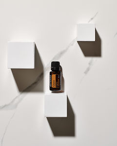 doTERRA Clove essential oil and white wooden blocks in sunlight with white marble background.