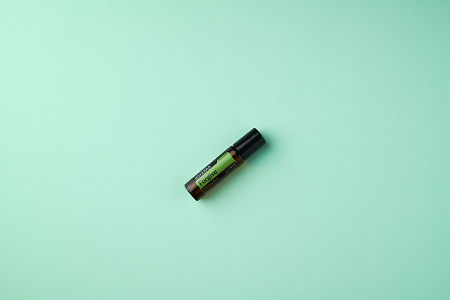 doTERRA Forgive Touch on a mint colored background.