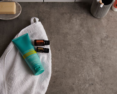 doTERRA Spa Hand and Body Lotion with Frankincense and Sandalwood essential oils and bathroom accessories on a white towel on a stone background.