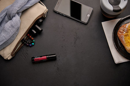 doTERRA Rose Touch with a leather clutch, roller bottles, cell phone, coffee and food on a black background.