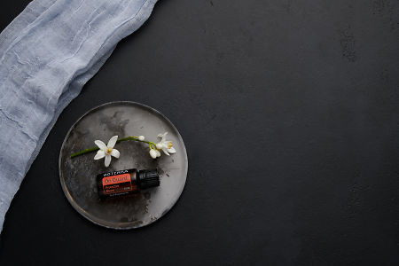 doTERRA On Guard with orange blossom flowers on a ceramic plate on a black concrete baclground.