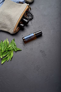 doTERRA Peppermint Touch with clutch, accessories and mint leaves on a black concrete background.