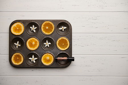 doTERRA Neroli Touch with seville orange slices and orange blossoms in a vintage baking tray on a white wooden background.