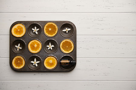 doTERRA  Citrus Bliss with seville orange slices and orange blossoms in a vintage baking tray on a white wooden background.