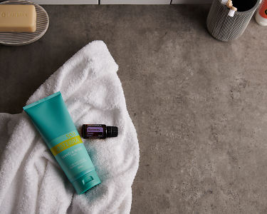 doTERRA Spa Hand and Body Lotion with Serenity essential oil blend and bathroom accessories on a white towel on a stone background.