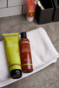 doTERRA Salon Essentials Shampoo and Conditioner with a white towel on a bathroom bench.
