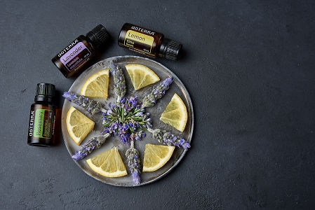 doTERRA Rosemary, Lavender and Lemon with a  rosemary flower, lavender flowers and lemon slices on a ceramic plate on a black concrete background.