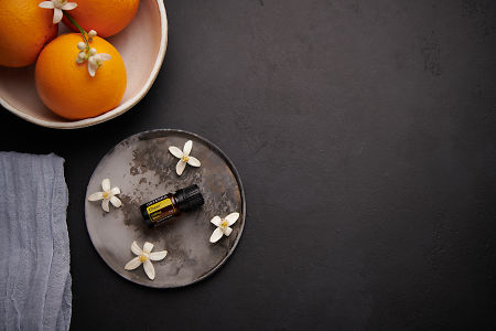 doTERRA Cheer with orange blossom flowers on a ceramic plate with a white ceramic bowl filled with seville oranges and orange blossoms on a black concrete background.