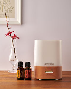 doTERRA Lumo diffuser with Citrus Bliss and On Guard essential oils on a side table.