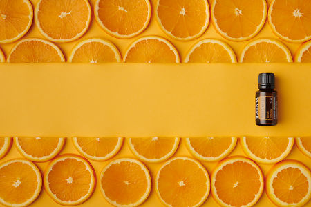 doTERRA Wild Orange oil and orange slices on orange paper background.
