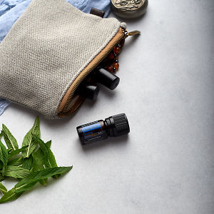 doTERRA Deep Blue with clutch, accessories and mint leaves on a white concrete background.