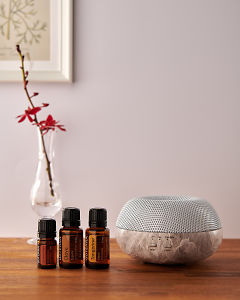 doTERRA Brevi Stone diffuser with Cinnamon, Clove and Tangerine essential oils on a side table.