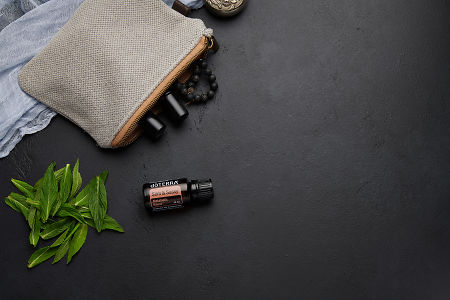 doTERRA Slim and Sassy  with clutch, accessories and mint leaves on a black concrete background.
