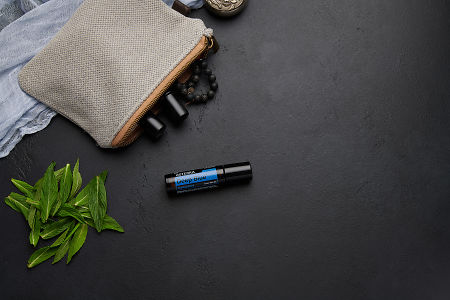 doTERRA Deep Blue Touch with clutch, accessories and mint leaves on a black concrete background.